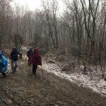 Résztvevők sétálnak a sáros, latyakos úton, melyet vékony hóréteg szegélyez